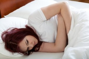 25324353 - upset woman lying in bed beacuse of stomachache
