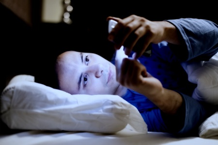 32258731 - man using his mobile phone in the bed