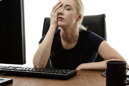 43401205 - woman sitting at her desk with her head in her hands stressed out