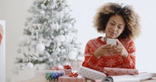 48510669 - young african woman checking for xmas messages on her mobile phone as she sits wrapping gifts in front of the christmas tree