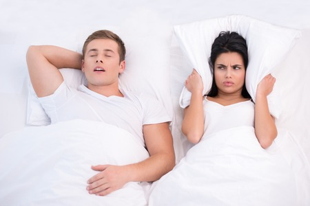 36619691 - top view photo of young couple lying in bed under white blanket. woman is angry because of snoring husband