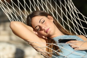37323106 - woman sleeping and resting on a hammock with a mobile phone on the chest