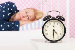 37848463 - blond woman of mature age with insomnia and big alarm clock - focus point on clock