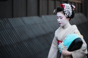 19886716 - kyoto, japan - april 8, 2013: geisha approaching a famous tea house in the gion district of kyoto. the geisha in gion are the highest ranked in japan.