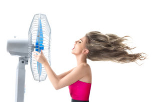 29337820 - young woman cooling face under wind of cooler fan isolated on white background