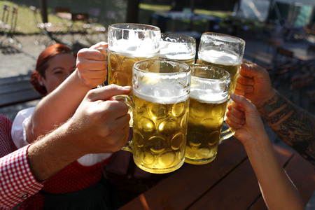 32084112 - people in traditional costumes drinking beer in a bavarian beer garden