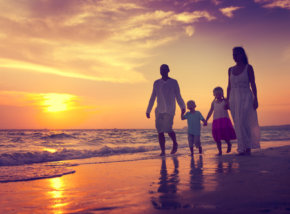38521259 - family walking beach sunset travel holiday concept