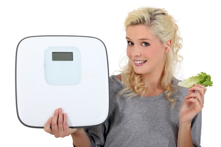 12302450 - blonde woman showing a bathroom scale and taking a lettuce leave