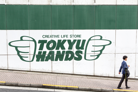 61559922 - tokyo, japan - 21 june 2016: a direction sign for the iconic tokyu hands store  points to a passerby, in shibuya, tokyo.
