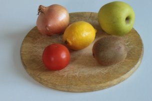 11839477 - five items of fruit and vegetables displayed on an old breadboard